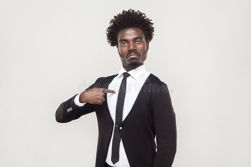 Uomo fiero ben vestito che esamina macchina fotografica con il fronte chesty fotografia stock libera da diritti
