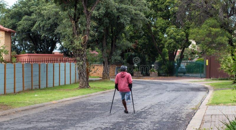 Uomo fisicamente disabile non identificato sulle grucce fotografie stock libere da diritti