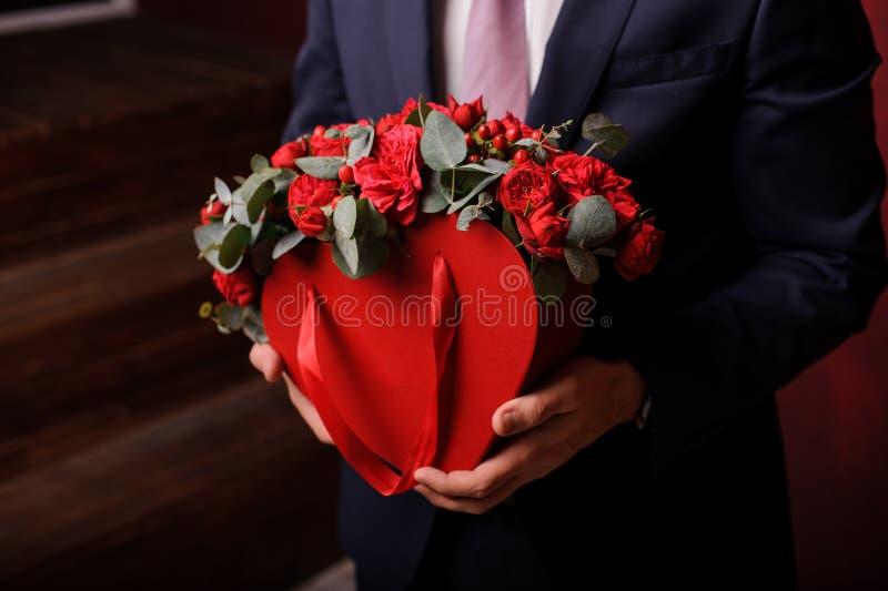 Uomo forte che tiene in una mano una scatola rossa di belle rose fotografie stock