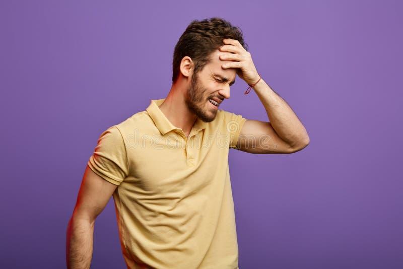 Uomo frustrato che ha problemi con la testa dopo il partito di notte Concetto di postumi di una sbornia fotografie stock libere da diritti