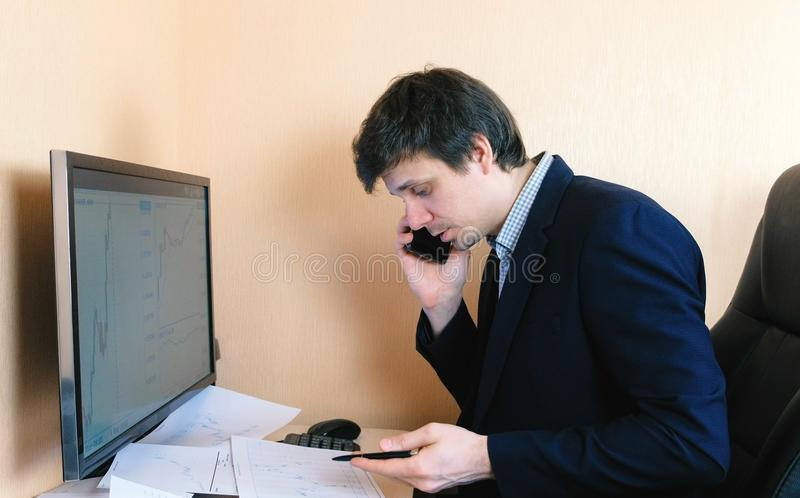 Download Uomo Frustrato Che Lavora Al Computer E Che Chiama Telefono Cellulare Confronta I Grafici Sullo Schermo E Su Carta Immagine Stock - Immagine di riservatezza, persona: 117982027