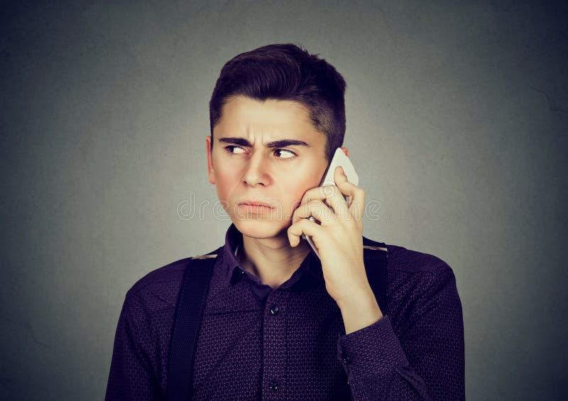 Uomo frustrato da qualcuno che ascolta sul telefono cellulare fotografia stock libera da diritti