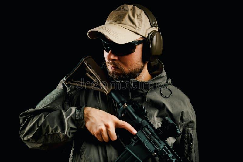 Uomo in fucile di assalto della tenuta del cappuccio fotografia stock