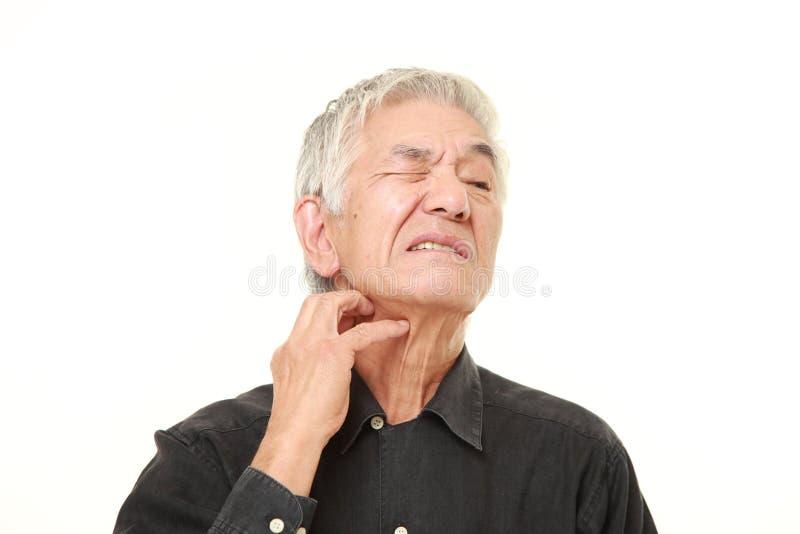 Uomo giapponese senior che graffia il suo collo fotografia stock libera da diritti