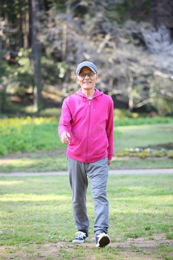 Uomo giapponese senior che indossa le passeggiate rosa del parka su un prato inglese fotografia stock libera da diritti