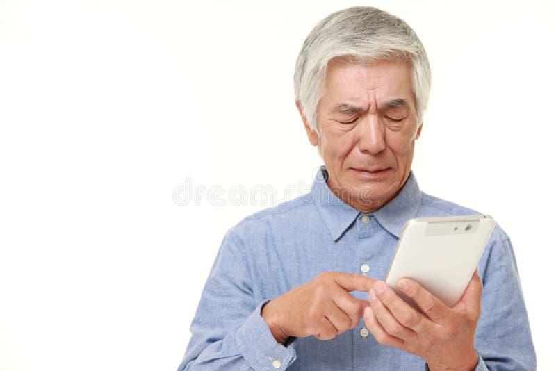 Uomo giapponese senior che per mezzo del computer della compressa che sembra sconcertante fotografia stock libera da diritti