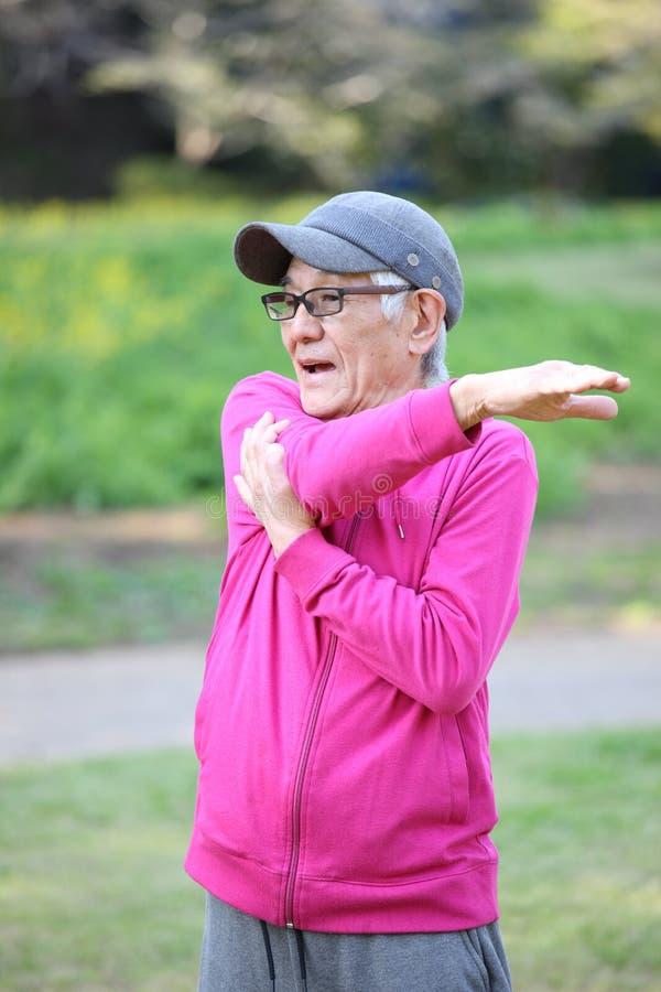 Uomo giapponese senior che porta parka rosa che fa allungamento del braccio all'aperto fotografia stock