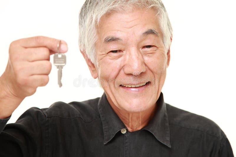 Uomo giapponese senior con la chiave domestica immagini stock libere da diritti