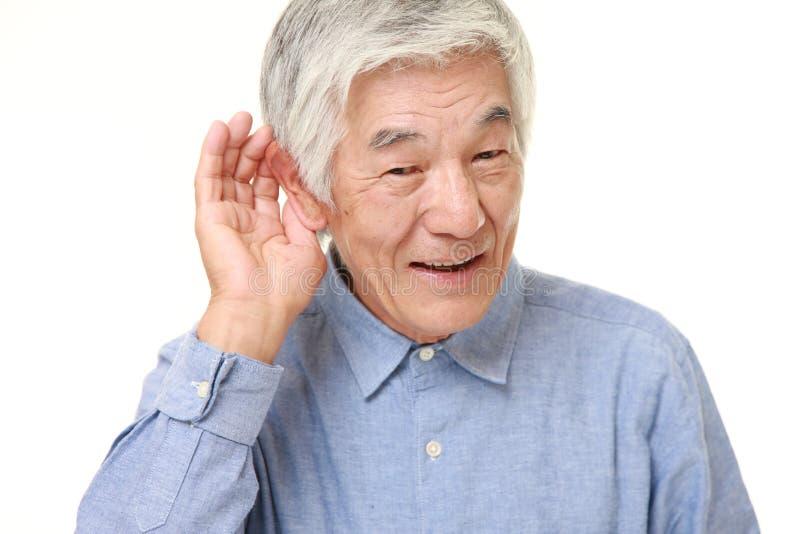 Uomo giapponese senior con la mano dietro l'orecchio che ascolta molto attentamente fotografie stock