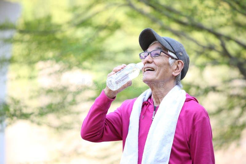 Uomo giapponese senior nell'usura di rosa sudata ed assetata dopo l'esterno dell'acqua delle bevande di esercizio immagine stock