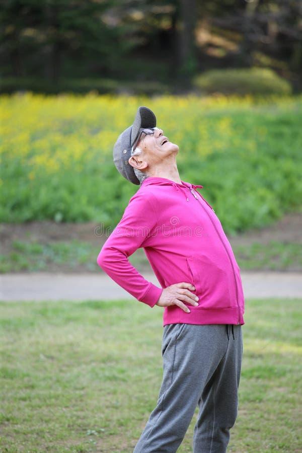 Uomo giapponese senior nell'usura rosa che fa esercizio fisico che sta indietro curvatura all'aperto fotografia stock