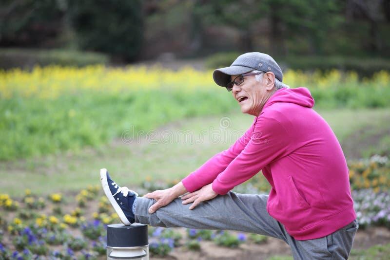 Uomo giapponese senior in una maglia con cappuccio che fa allungamento stante del tendine del ginocchio immagini stock libere da diritti
