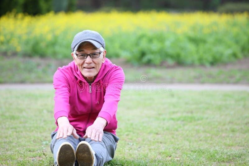 Uomo giapponese senior in una maglia con cappuccio che fa curvatura di andata di seduta fotografia stock libera da diritti