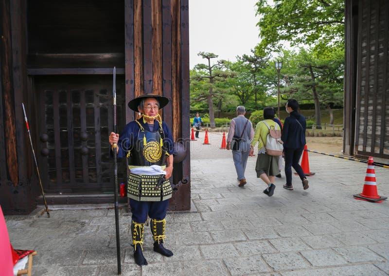 Uomo giapponese in un costume del samurai al portone del castello di Himeji, Giappone fotografia stock