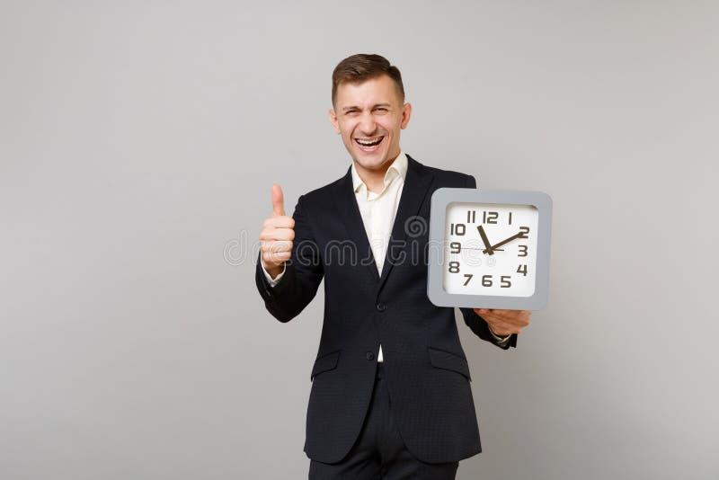 Uomo giovane di risata di affari in vestito nero classico, camicia bianca che tiene orologio quadrato, mostrante pollice sull'iso fotografia stock libera da diritti