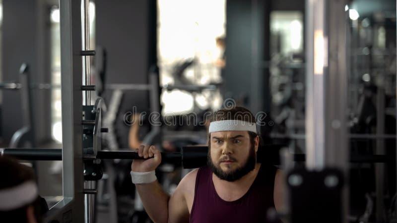 Uomo grasso appena che fa esercizio con il bilanciere in palestra, allenamento di forma fisica, perdita di peso immagini stock