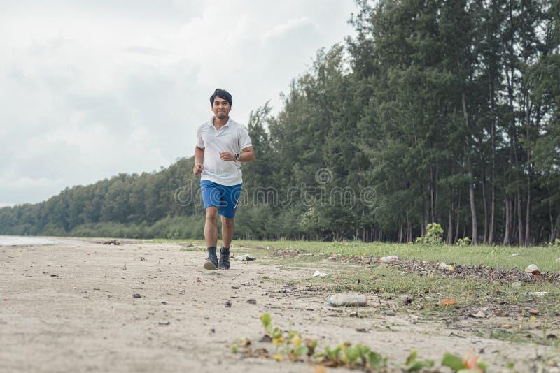 Uomo grasso che corre sulla spiaggia fotografia stock