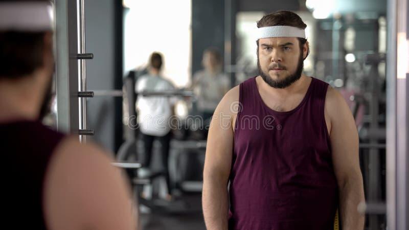 Uomo grasso che esamina riflessione di specchio in palestra, addestramento mentale prima dell'allenamento fotografie stock libere da diritti