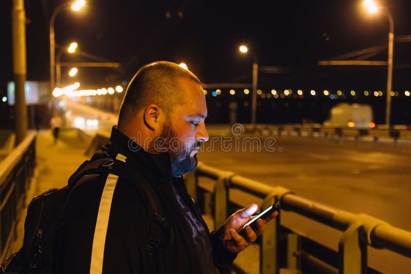 Uomo grasso che per mezzo dello smartphone sul ponte alla città di notte immagini stock