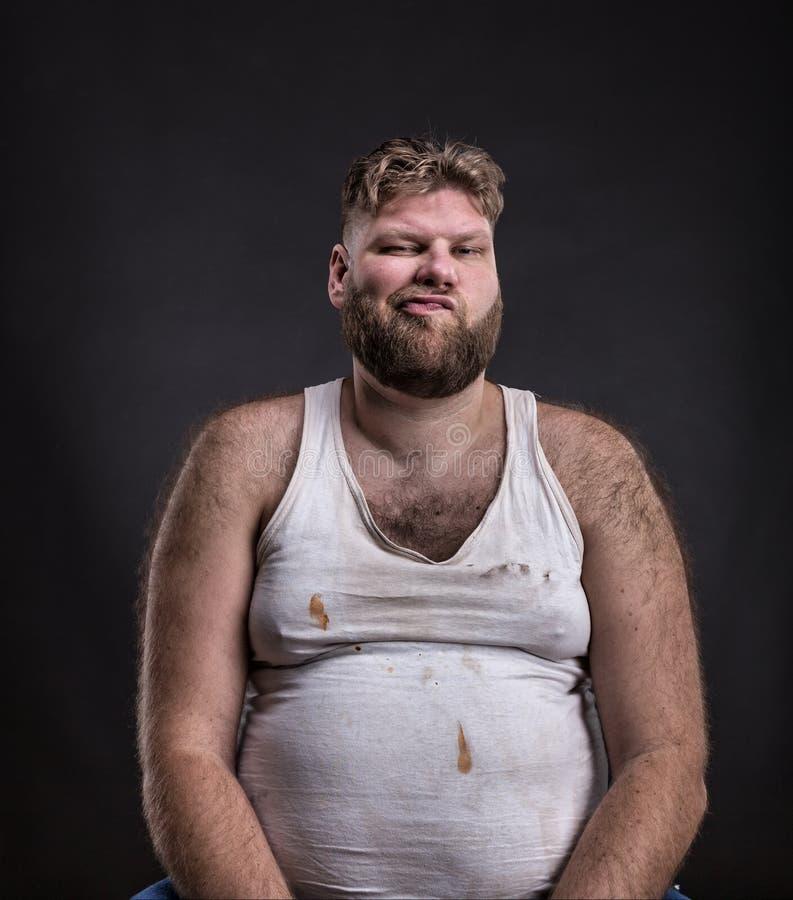 Uomo grasso con la barba in camicia sporca fotografia stock libera da diritti