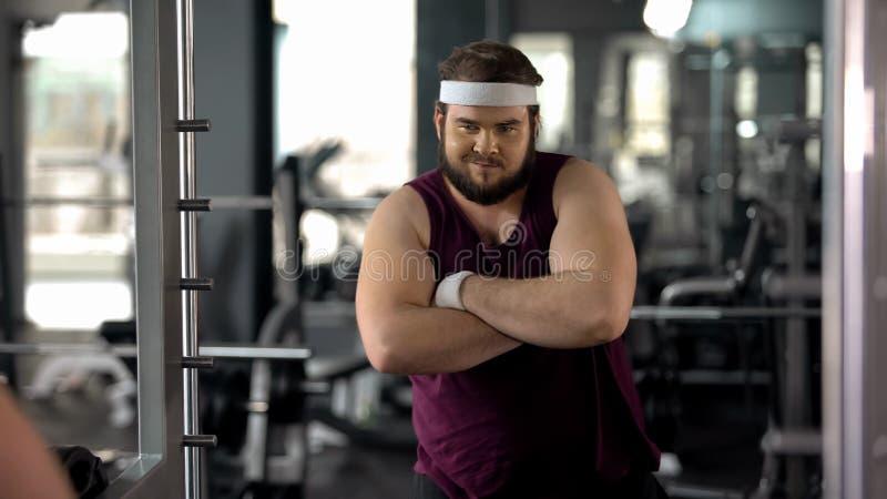Uomo grasso con le mani piegate che esaminano specchio, soddisfatto con i risultati di perdita di peso immagine stock