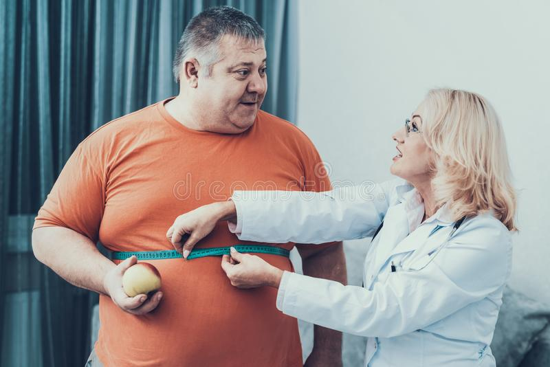 Uomo grasso con medico in camice in Gray Room immagini stock