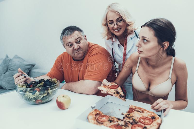 Uomo grasso di seduta e giovane ragazza anoressica con alimento immagine stock libera da diritti
