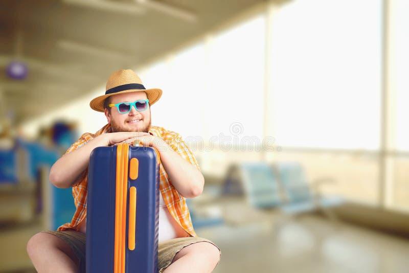 Uomo grasso divertente con una valigia in aeroporto per il viaggio sulla vacanza di estate fotografia stock