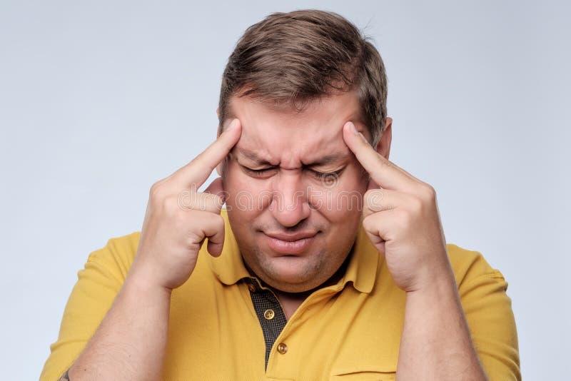 Uomo grasso sollecitato in maglietta gialla con le dita sul tempio che soffre dall'emicrania fotografia stock