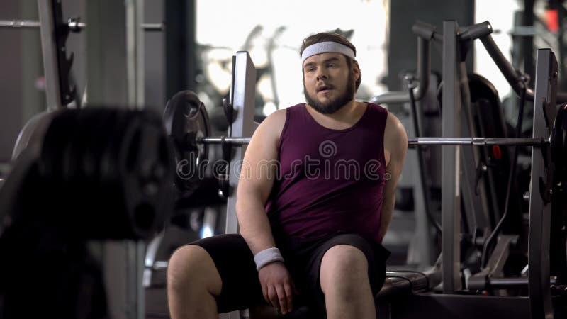 Uomo grasso stanco che ha resto dopo l'esercizio di allenamento, forza dei muscoli, preparantesi immagini stock libere da diritti