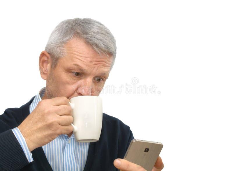 Uomo grigio-dai capelli sorpreso di affari maturi che esamina il suo smartphone isolato su bianco immagine stock libera da diritti