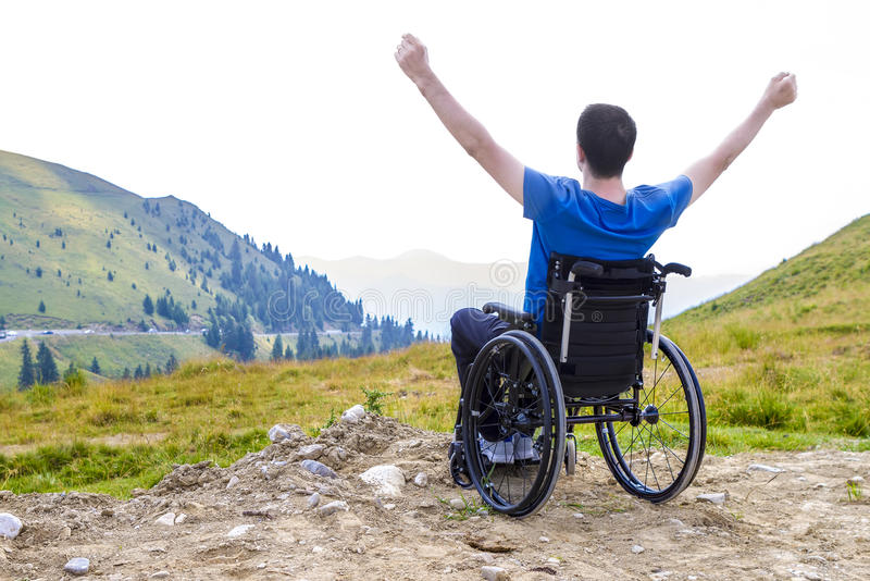 Uomo handicappato ottimista che si siede sulla sedia a rotelle immagine stock libera da diritti