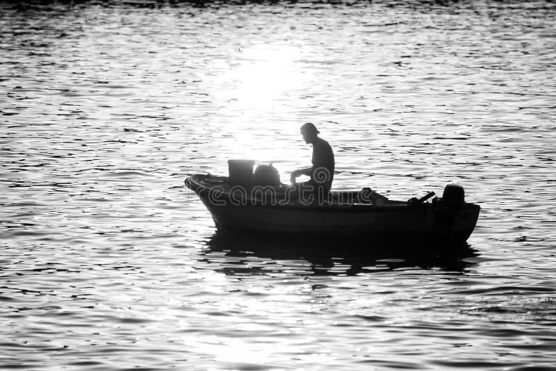 Uomo in imbarcazione a motore al bw di tramonto immagini stock libere da diritti