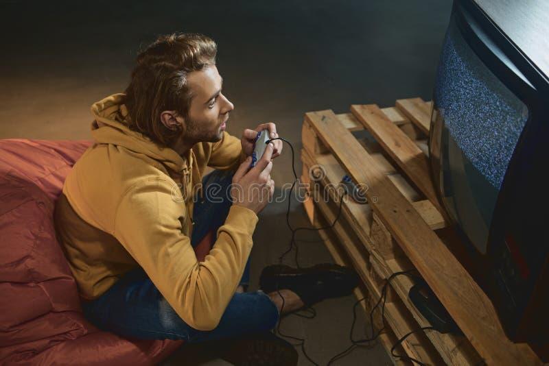 Uomo impegnato che gioca in video gioco fotografie stock