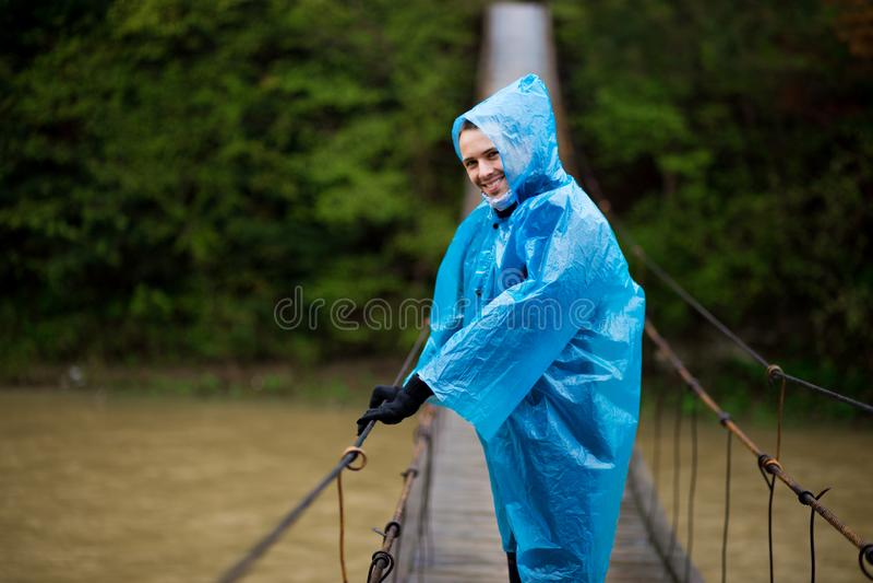 Uomo in impermeabile giallo che cammina nella foresta di conifere durante il piovoso immagini stock
