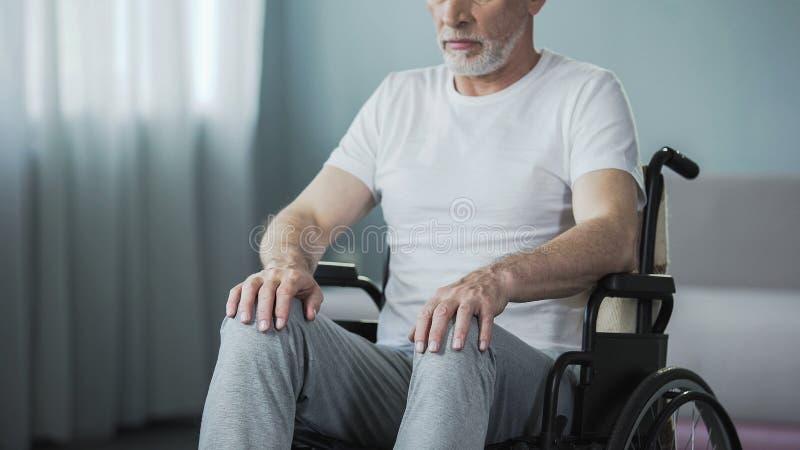 Uomo impotente con le inabilità che si siedono in sedia a rotelle e che provano a muoversi, salute fotografia stock