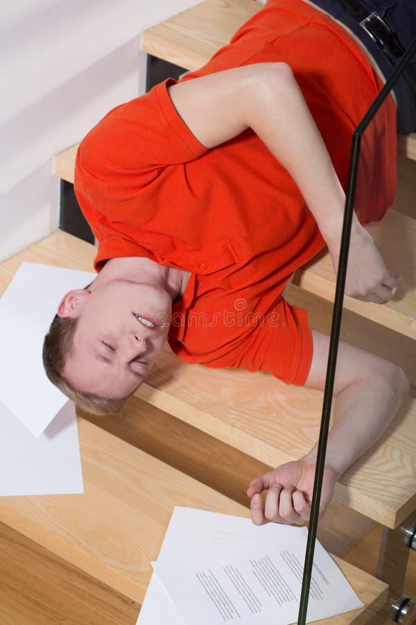 Uomo incosciente che si trova sulle scale immagini stock