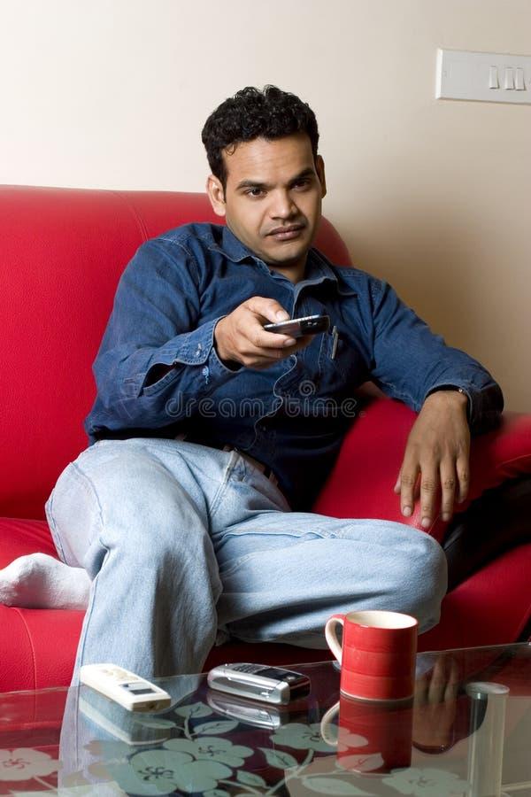 Uomo indiano annoiato con telecomando fotografia stock libera da diritti