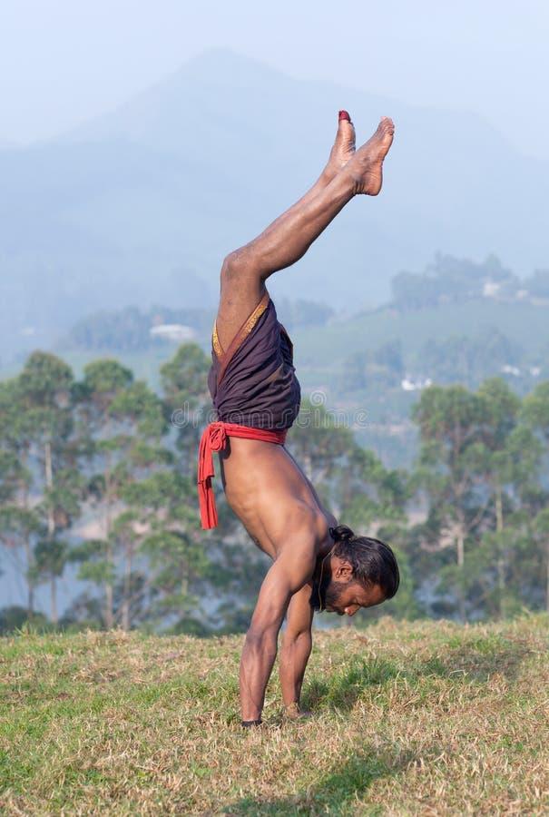 Uomo indiano che fa verticale all'aperto nel Kerala, India del sud immagine stock