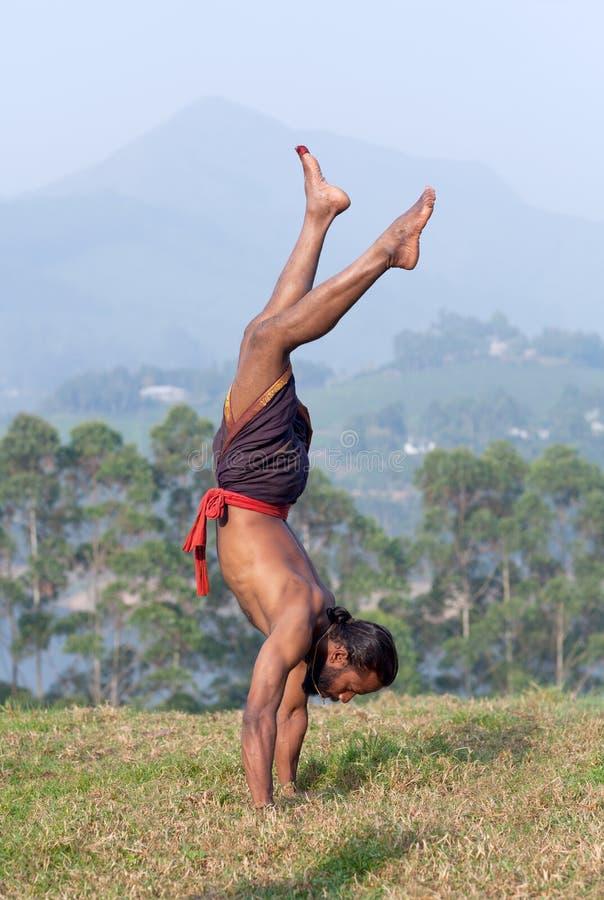 Uomo indiano che fa verticale all'aperto nel Kerala, India del sud fotografie stock libere da diritti