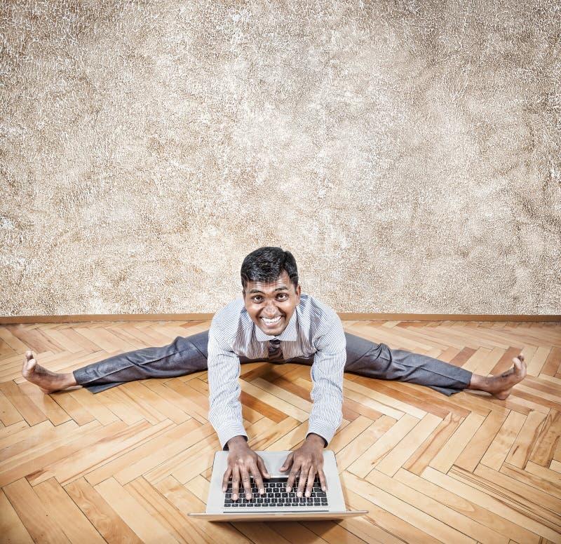 Uomo indiano che fa yoga con il computer portatile fotografia stock