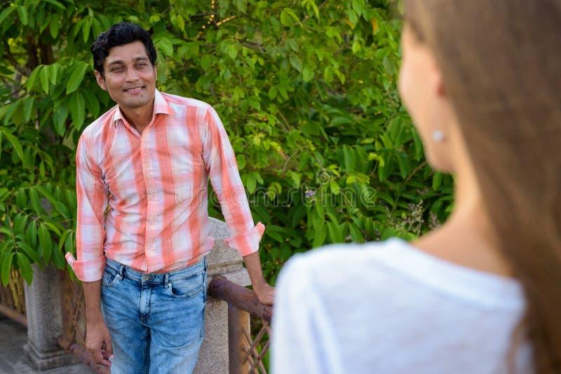 Uomo indiano felice che sorride e che esamina bella donna nell'amore fotografie stock