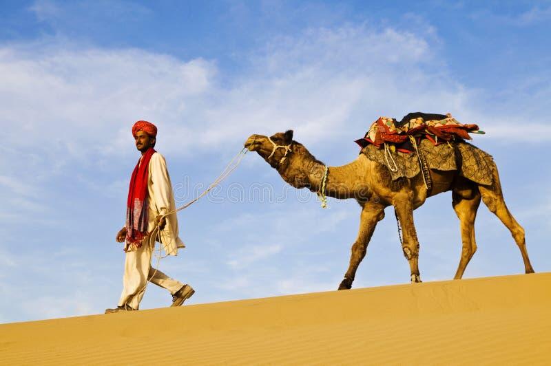 Uomo indiano indigeno che cammina attraverso il deserto con il suo cammello fotografia stock libera da diritti