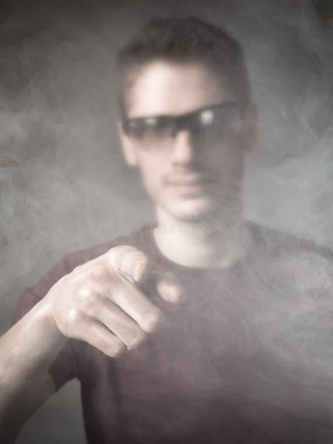 Download Uomo Indicato In Una Nuvola Di Fumo Fotografia Stock - Immagine di espressioni, fantasma: 56878800