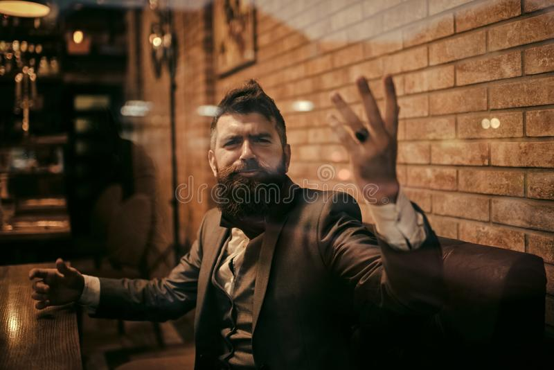 Uomo indignato in un ristorante Uomo d'affari con la barba lunga nel club del sigaro Il cliente sicuro della barra si siede in ca immagini stock