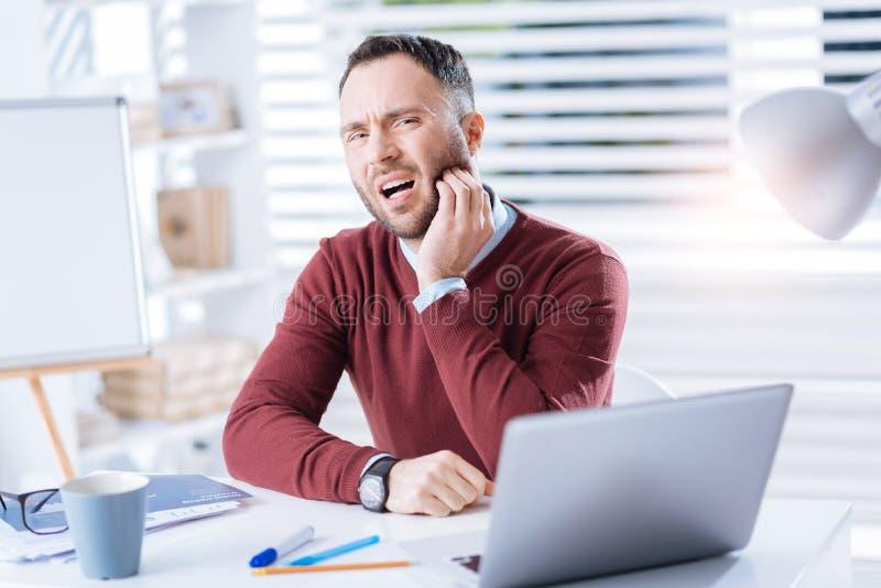Uomo infelice che ritiene mal di denti terribile mentre lavorando nel suo ufficio fotografia stock
