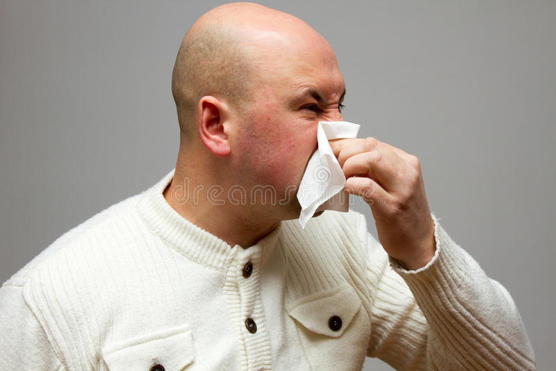 Uomo infettato che soffia il suo naso in carta velina a causa dell'essere malato su fondo grigio fotografia stock libera da diritti