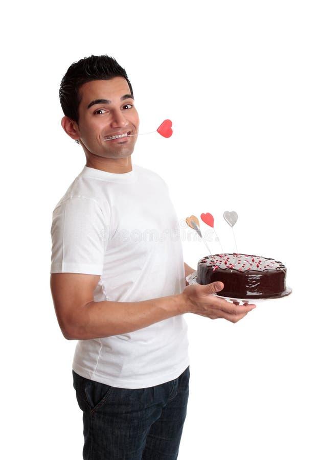 Uomo insolente con una torta del cuore di amore fotografie stock libere da diritti