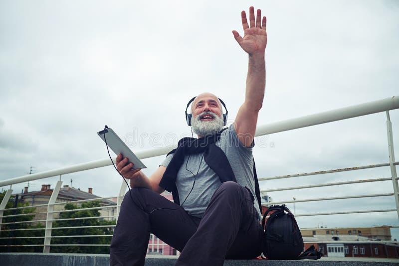 Uomo invecchiato alla moda in cuffie che ondeggiano la suoi mano e sorridere immagini stock libere da diritti