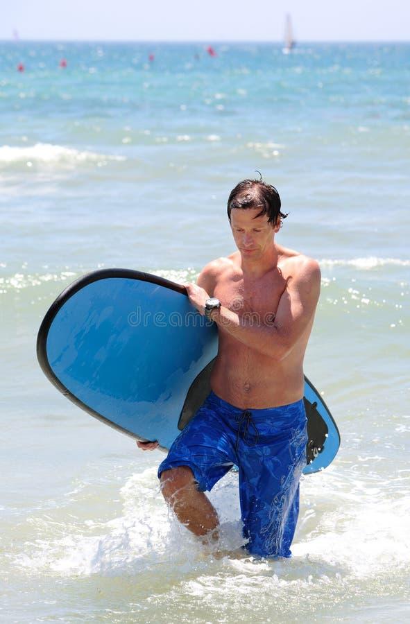 Uomo invecchiato centrale adatto che pratica il surfing sulla spiaggia in estate fotografia stock